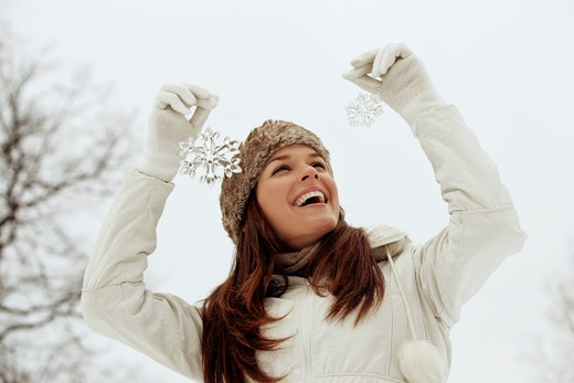 Stock Photo: 1804R-20917 A young woman holding two snowflake decorations