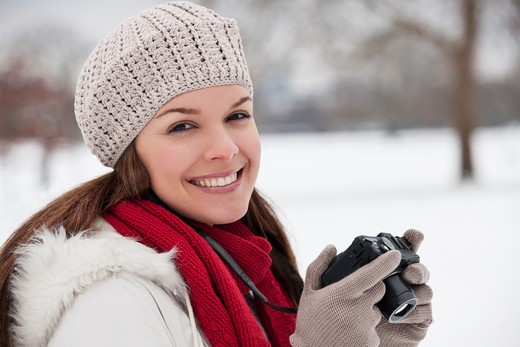 A young woman standing in the snow, holding a camera : Stock Photo