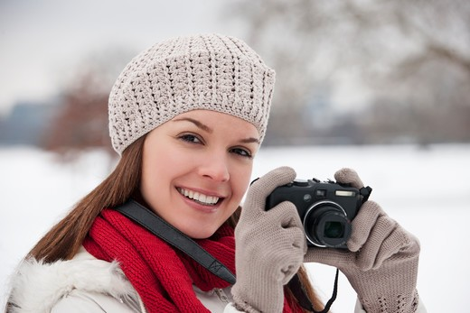Stock Photo: 1804R-20935 A young woman standing in the snow, taking a photograph