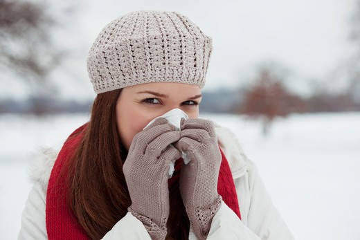 Stock Photo: 1804R-20942 A young woman standing in the snow, blowing her nose