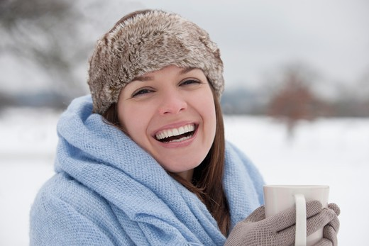 Stock Photo: 1804R-20947 A young woman standing in the snow, holding a hot drink, laughing