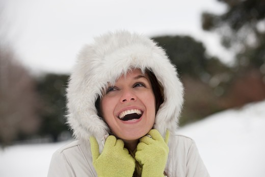 A young woman standing in the snow, laughing : Stock Photo