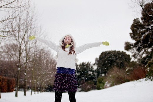 A young woman standing in the snow with her arms outstretched : Stock Photo
