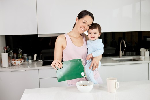 A young mother holding her baby son whilst making breakfast : Stock Photo