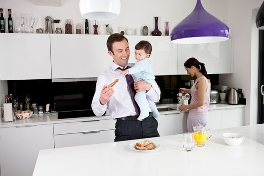 Stock Photo: 1804R-20962 A father trying to eat his breakfast whilst holding his baby son