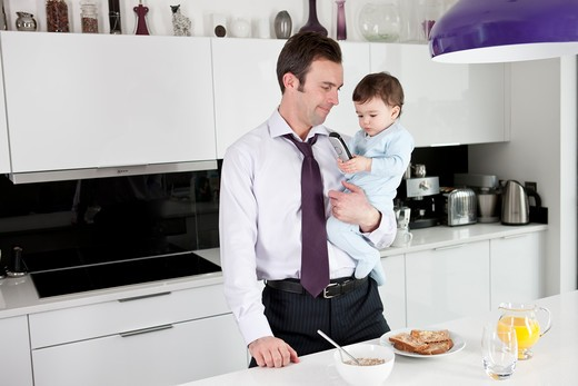 A father trying to use the telephone whilst holding his baby son : Stock Photo
