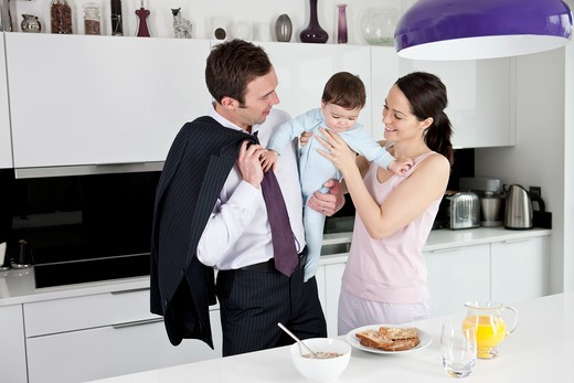 Stock Photo: 1804R-20970 A couple and their baby son in the kitchen, father going off to work