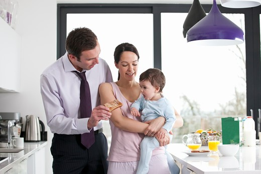 Stock Photo: 1804R-20975 A couple and their baby son in the kitchen at breakfast time