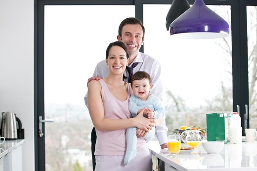 A couple and their baby son in the kitchen at breakfast time : Stock Photo