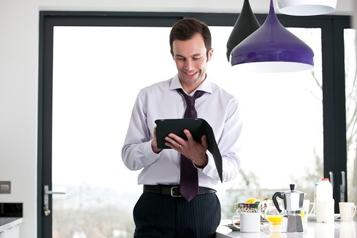 Stock Photo: 1804R-20978 A businessman standing in a kitchen using a digital tablet