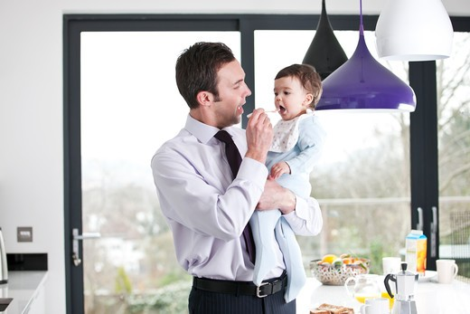 A father feeding his baby son breakfast : Stock Photo