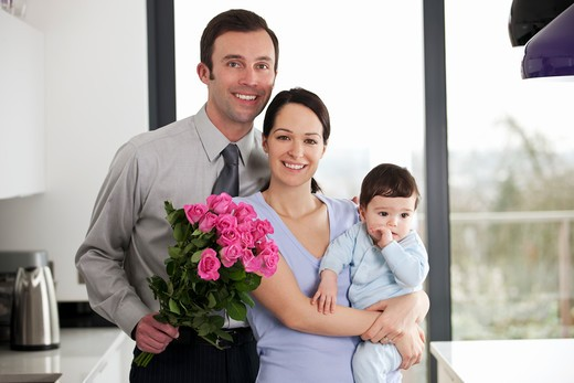 Stock Photo: 1804R-21006 A man giving his partner a bunch of roses, woman holding their baby son