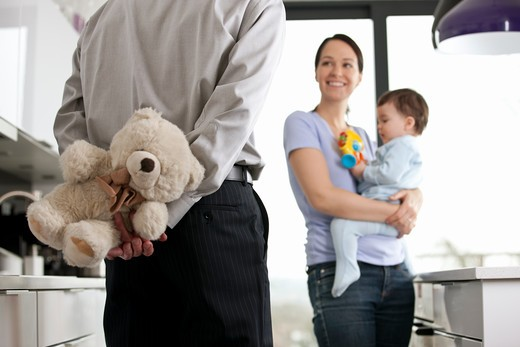 Stock Photo: 1804R-21007 A man returning home to his family after work, holding a teddy bear behind his back