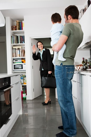 A mother leaving for work, waving goodbye to her partner and baby son : Stock Photo