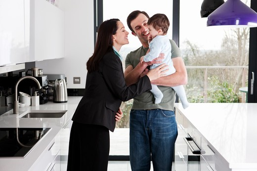 A working mother greeting her partner and baby son : Stock Photo