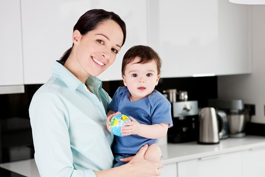 A mother with her baby son, baby holding a globe ball : Stock Photo