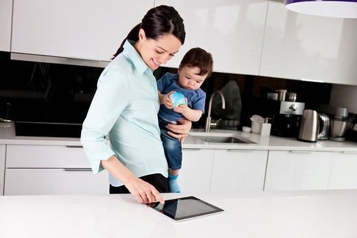 A mother and her baby son looking at a digital tablet, baby holding a globe ball : Stock Photo