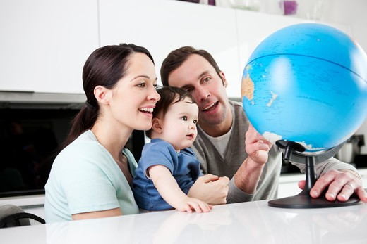 Stock Photo: 1804R-21028 A couple and their baby son looking at a globe