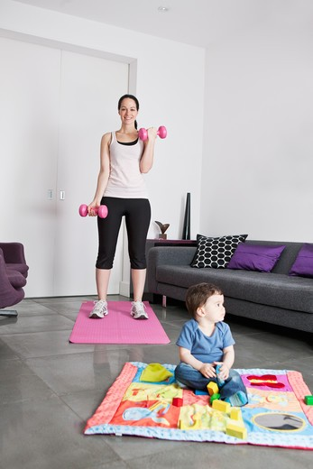 A young mother exercising at home whilst her baby son plays on the floor : Stock Photo