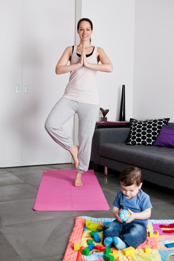 Stock Photo: 1804R-21041 A young mother practicing yoga at home whilst her baby son plays on the floor