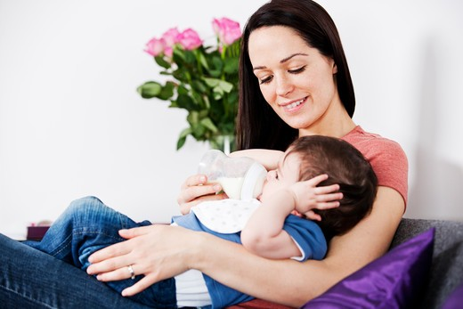 Stock Photo: 1804R-21045 A mother feeding her baby son a bottle of milk