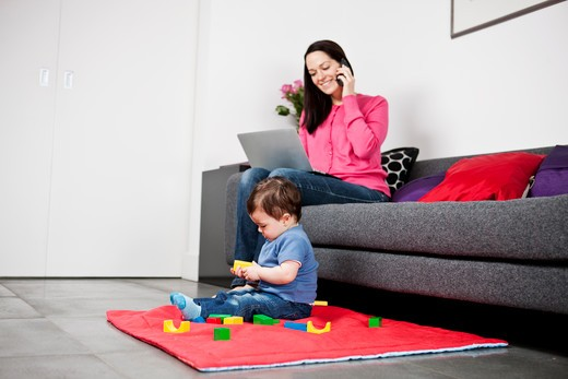 Stock Photo: 1804R-21055 A mother using a laptop and talking on the phone, baby son playing at her feet