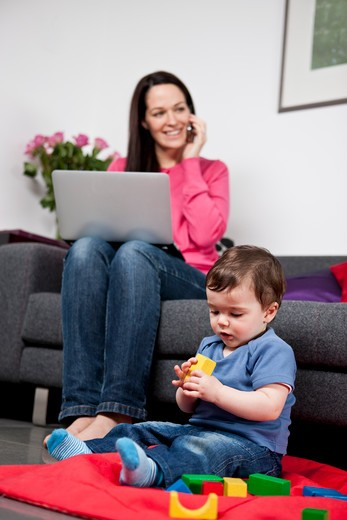 Stock Photo: 1804R-21056 A woman using a laptop and talking on a mobile phone at home