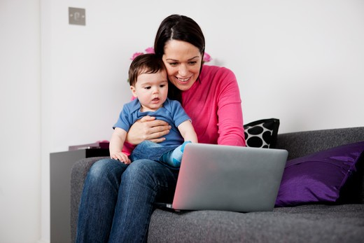 Stock Photo: 1804R-21059 A mother and her baby son sitting on a sofa looking at a laptop