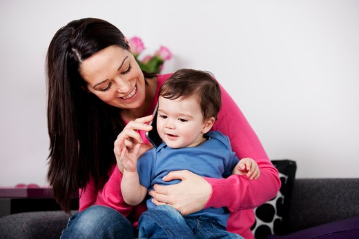 Stock Photo: 1804R-21062 A mother and her baby son listening on a mobile phone