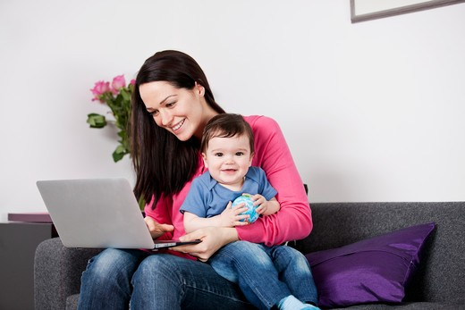A mother using a laptop whilst holding her baby son on her lap : Stock Photo