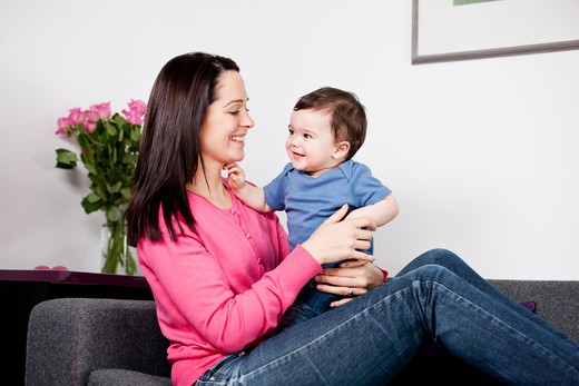 A mother sitting on a sofa holding her baby son : Stock Photo