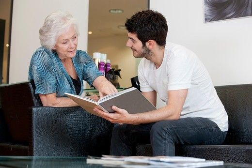 A senior woman looking a book of hairstyles with a male hairdresser : Stock Photo
