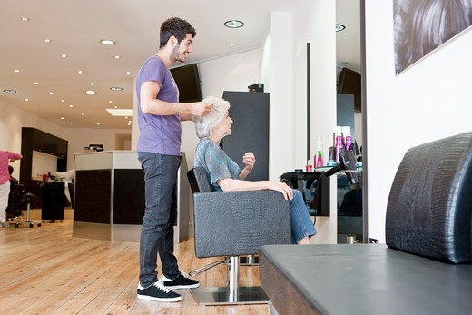 A male hairdresser discussing a female clients hair : Stock Photo