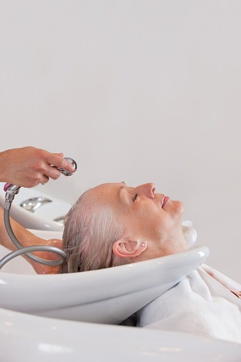 A senior woman having her hair washed at hairdressing salon, close up : Stock Photo