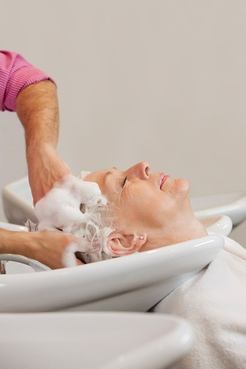 Stock Photo: 1804R-21085 A senior woman having her hair shampooed at a hairdressing salon, close up