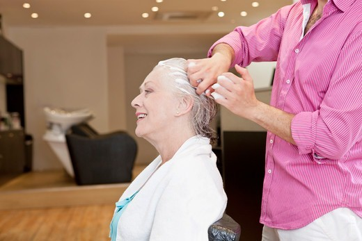 A male hairdresser applying product to his female clients hair, close up : Stock Photo