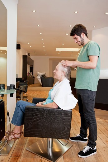Stock Photo: 1804R-21090 A male hairdresser applying product to his female clients hair
