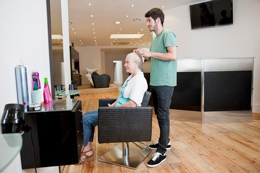A male hairdresser applying product to his female clients hair : Stock Photo