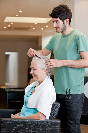 Stock Photo: 1804R-21093 A male hairdresser combing a female clients hair