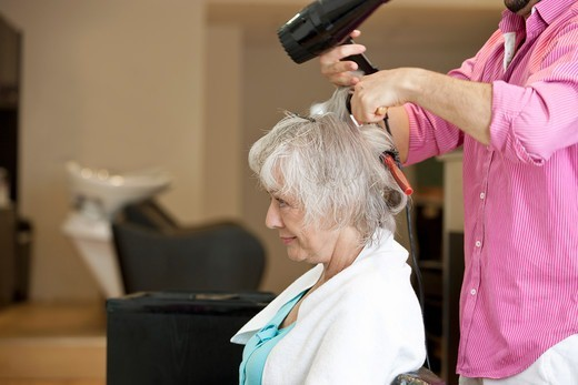 Stock Photo: 1804R-21094 A senior woman having her blow dried at a hairdressing salon