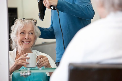 A senior woman drinking a hot beverage whilst having her hair dried : Stock Photo