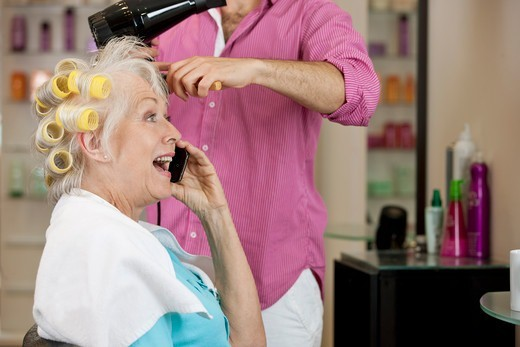 Stock Photo: 1804R-21097 A senior woman talking on a mobile phone whilst having her hair dried