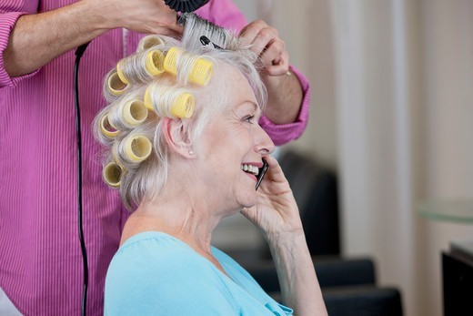 Stock Photo: 1804R-21098 A senior woman talking on a mobile phone whilst having her hair dried