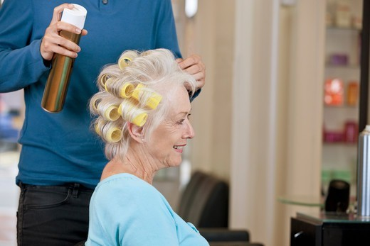 A male hairdresser applying hairspray to a female clients hair, close up : Stock Photo