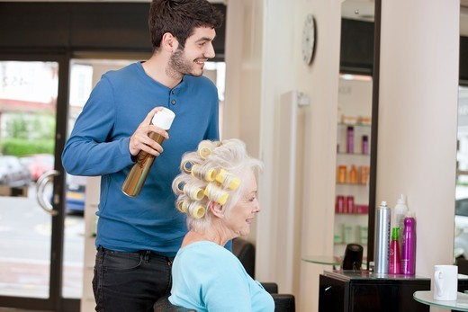 Stock Photo: 1804R-21103 A male hairdresser applying hairspray to a female clients hair