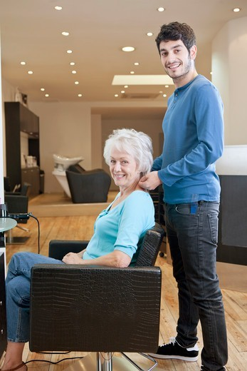 A male hairdresser and female client in a hairdressing salon : Stock Photo