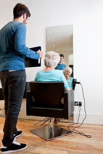 Stock Photo: 1804R-21110 A male hairdresser showing his client her new hairstyle in a mirror
