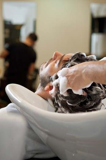 Stock Photo: 1804R-21115 A male hairdresser shampooing a male clients hair