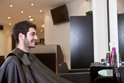 A male client looking at himself in the mirror of a hairdressing salon : Stock Photo