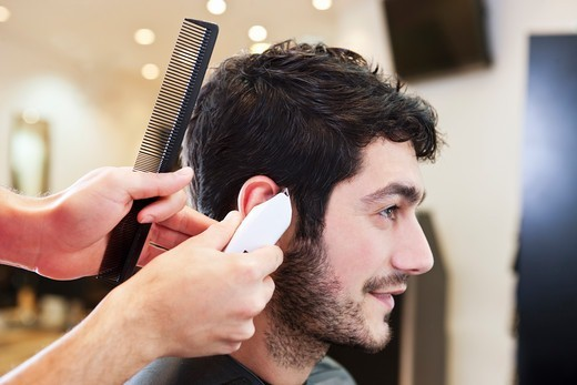 Stock Photo: 1804R-21120 A male hairdresser cutting his male clients hair with a shaver